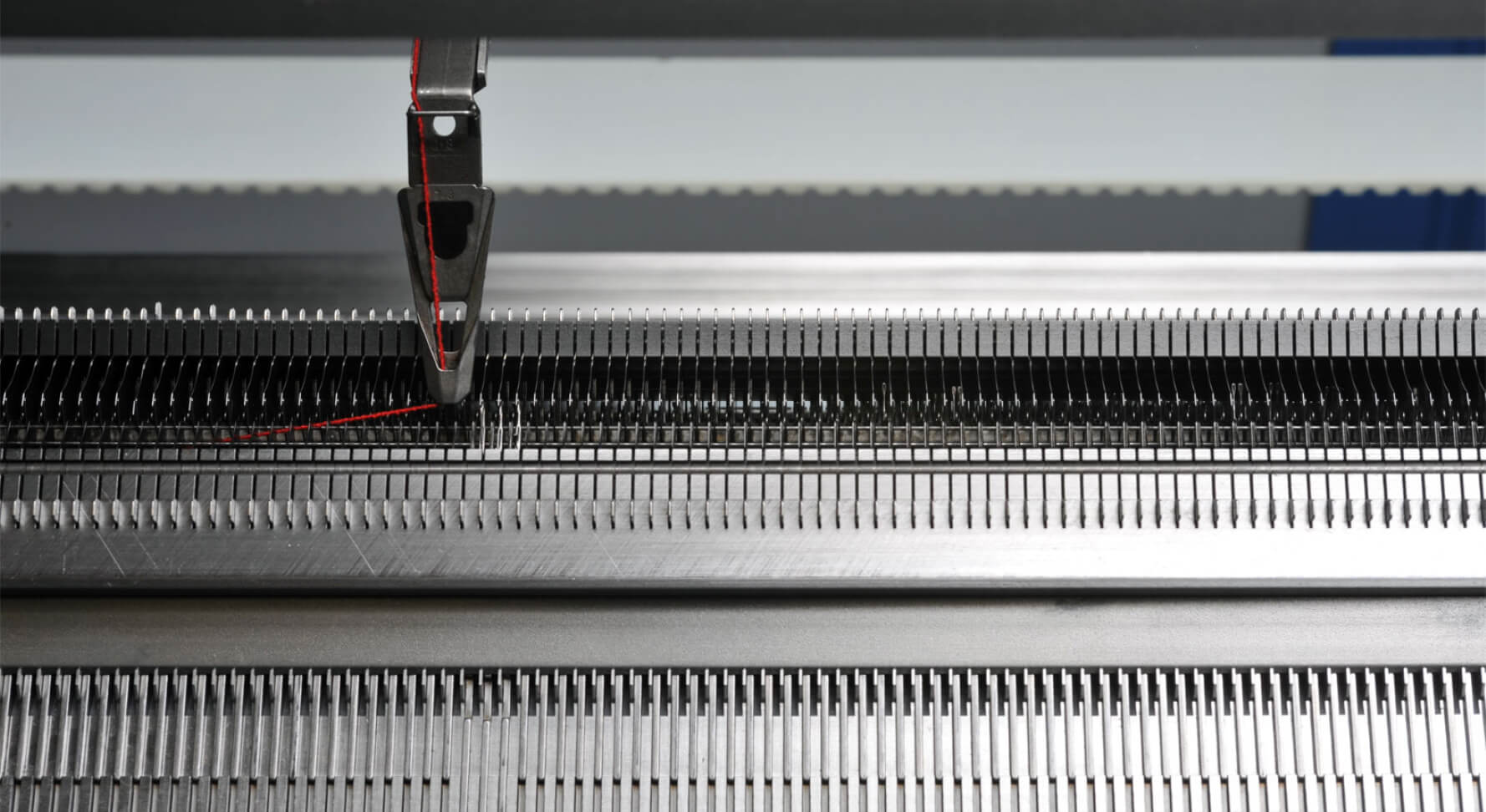Flat knitting machine with yarn carrier. One read thread is being knitted.
